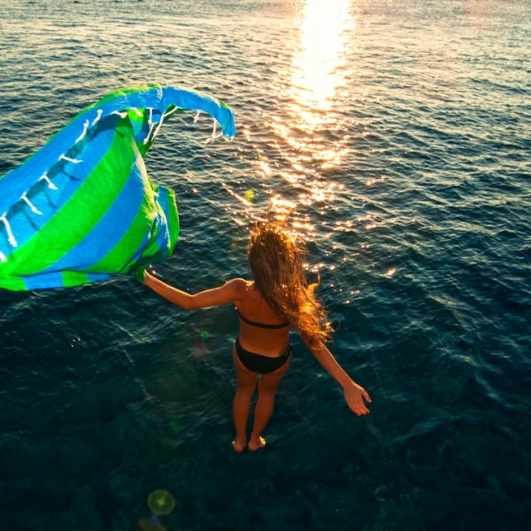 girl diving into sea with a brightly coloured Hammamas towel